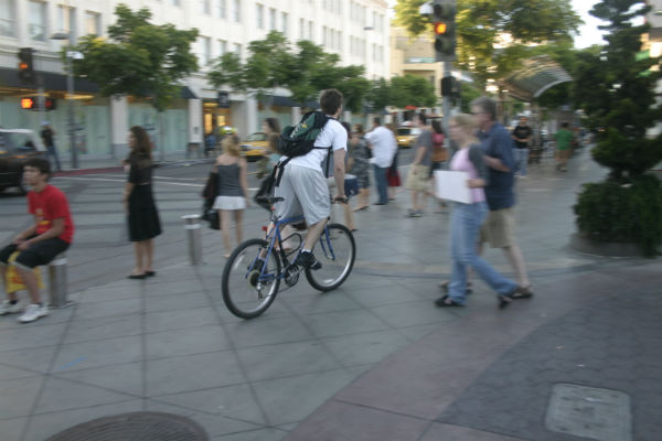 A cyclist, cycling through a street with pedestrians
